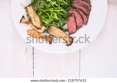 Beef fillet with mushrooms and Arugula on white wooden table , top view - stock photo