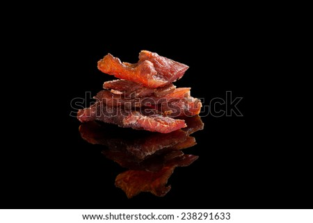 Beef jerky. Dry meat pieces isolated on black background. Delicious, culinary meat eating. - stock photo
