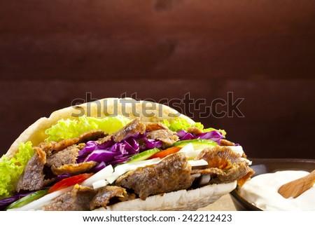 Beef Kebab in a bun on woodboard - stock photo