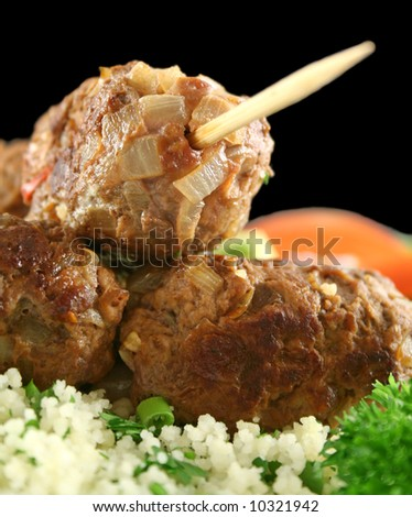 Beef kofta on parsley couscous with a garden salad. - stock photo