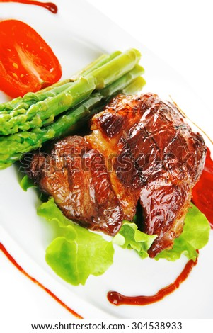 beef meat served on white plate with asparagus - stock photo