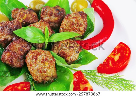 beef meatballs on basil with tomatoes and hot pepper - stock photo