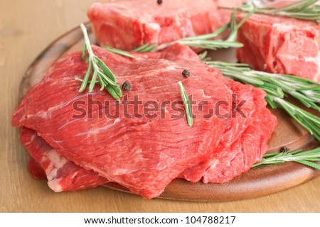 Beef Medallions Marinated with Rosemary and Peppercorns on Cutting Board - stock photo