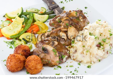 Beef medallions served with mushroom sauce, vegetable medley, potatoes, and hush puppies. - stock photo