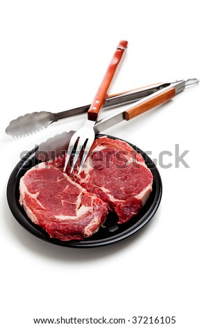 Beef ribeye steaks with cooking utensils on a white background - stock photo