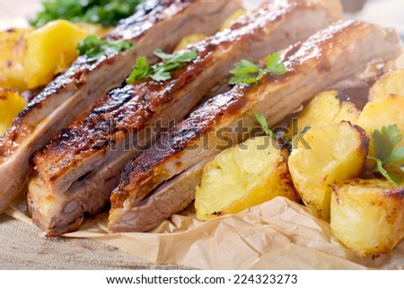 Beef ribs in bbq sauce and baked potatoes,selective focus - stock photo
