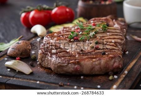 Beef rump steak on black stone table, close-up. - stock photo