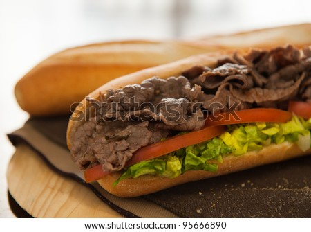 Beef sandwich with tomato and salad on a table. Very shallow depth of field. - stock photo