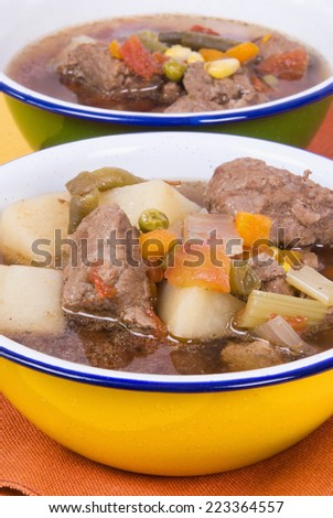 beef soup made of  potatoes, mixed vegetables, low sodium beef broth, onions, celery, garlic and various herbs and spices. Homemade. Shallow definition of field with focus on the front bowl.  - stock photo
