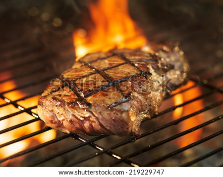beef steak cooking over flaming grill - stock photo