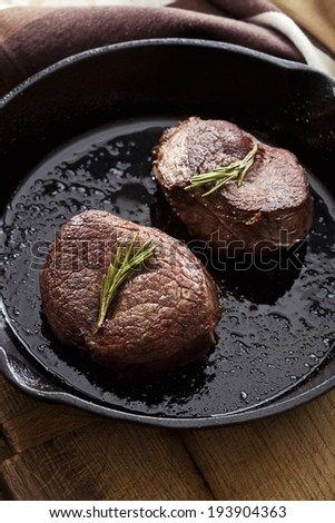 Beef steak in pan on wooden background - stock photo