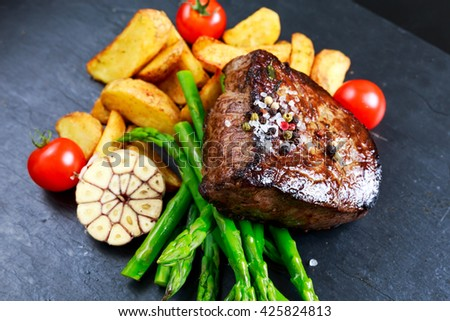 Beef steak Mignon cooked with Asparagus, potatoes, garlic and tomatoes.  - stock photo