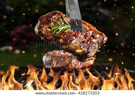 Beef steak on grill in fire with black background - stock photo
