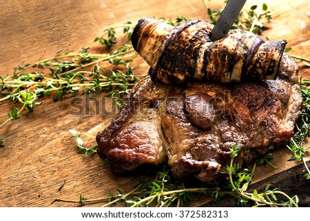 Beef steak. Piece of  Grilled BBQ beef marinated in spices with eggplant and herbs on a rustic wooden board over rough wooden desk with a copy space. Top view - stock photo