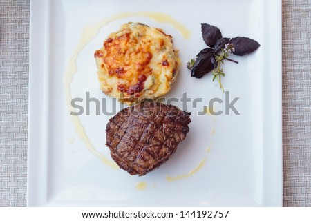 Beef steak with a potato gratin on a plate - stock photo
