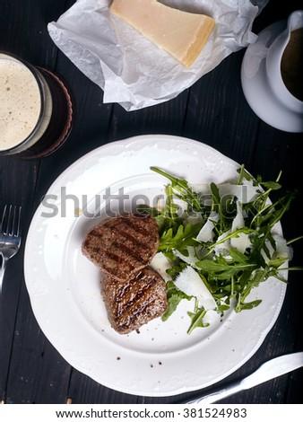 Beef steak with arugula salad in white plate on dark wood background - stock photo