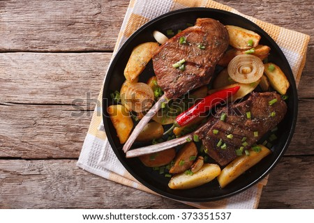 Beef steak with chili and fried potatoes on a plate. horizontal top view