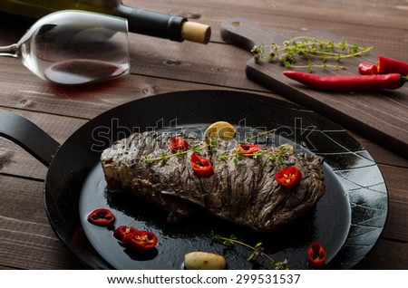 Beef steak with herbs and chilli, product photo with wine for client - stock photo