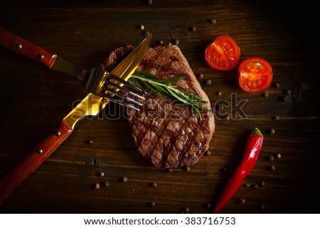 beef steak with herbs and vegetables on wooden table - stock photo