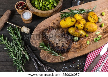 Beef steak with roasted potatoes and herbs, top view - stock photo