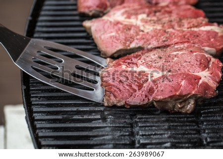 Beef steaks being prepared on grill or BBQ with pepper, spices and seasoning with spatula - stock photo