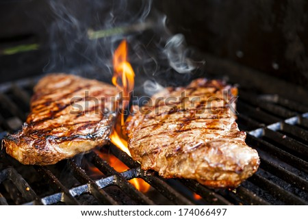 Beef steaks cooking in open flame on barbecue grill - stock photo