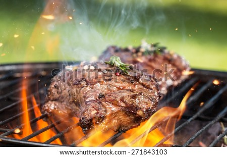 Beef steaks on grill - stock photo