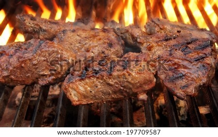 Beef steaks on the flaming grill. - stock photo