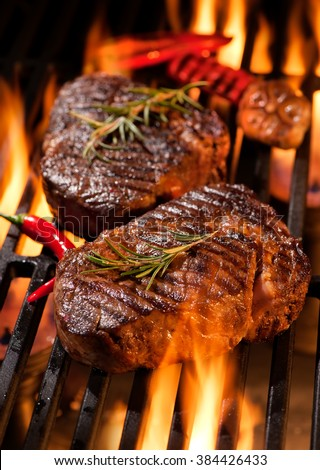 Beef steaks on the grill with flames - stock photo