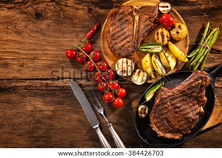 Beef steaks with grilled vegetables and seasoning on wood - stock photo