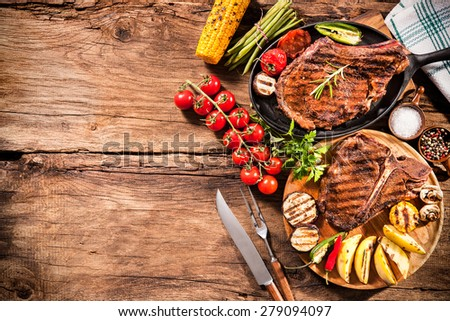 Beef steaks with grilled vegetables and seasoning on wooden background - stock photo