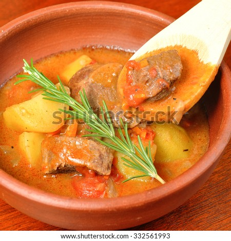 beef stew over a wooden board - stock photo