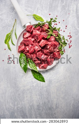 Beef stew prepared  for goulash cooking in white pan with fresh seasoning and spices, top view, place for text - stock photo