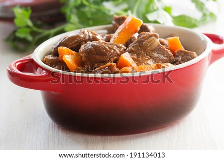 Beef stew with carrot. Traditional french beef goulash in red ceramic pot - stock photo