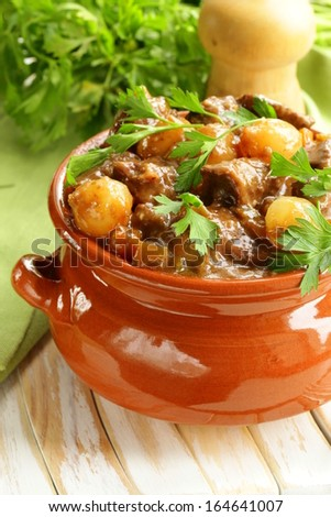 Beef stew with vegetables and herbs in a clay pot - comfort food - stock photo