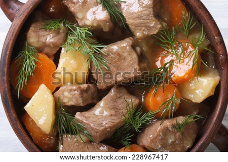 beef stew with vegetables and herbs in a pot macro. background horizontal view from the top.  - stock photo