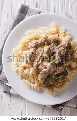 beef stroganoff and pasta fusilli close-up on a plate on the table. Vertical view from above
