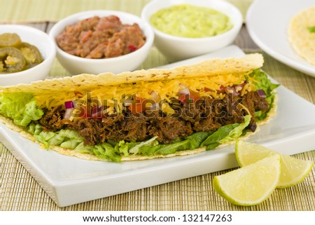Beef Tacos - Mexican shredded beef tacos in soft corn tortillas served with lettuce, sour cream, grated cheddar cheese and salsa. Guacamole, refried beans and jalape�±os on the background. - stock photo