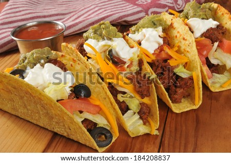 Beef tacos with sour cream, guacamole and cheddar cheese - stock photo