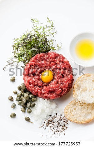 Beef tartare with capers and fresh onions on white background - stock photo