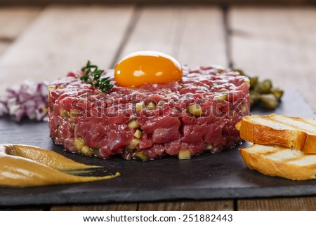 Beef tartare with capers yolk and mustard - stock photo