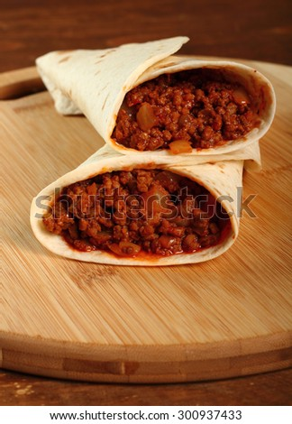 Beef tortilla with chili sauce. Enchilada. - stock photo