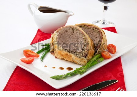 Beef Wellington - delicious roasted beef tenderloin rolled in mushroom puree and prosciutto, then wrapped in puff pastry. Garnished with green beans, tomatoes, and asparagus.  - stock photo