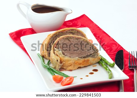 Beef Wellington - delicious roasted beef tenderloin rolled in mushroom puree and prosciutto, then wrapped in puff pastry. Garnished with green beans, tomatoes, and asparagus. Christmas ornaments.  - stock photo