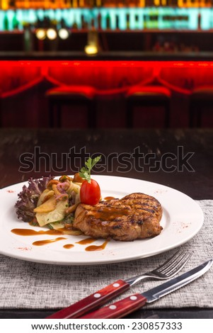 Beefsteak garnished with potatoes and mushrooms on table at the bar - stock photo