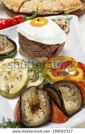 Beefsteak with egg and grilled vegetables on the plate. - stock photo