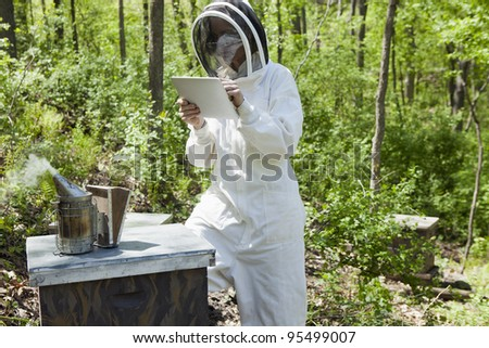 Beekeeper taking notes on a digital tablet at the beehive - stock photo