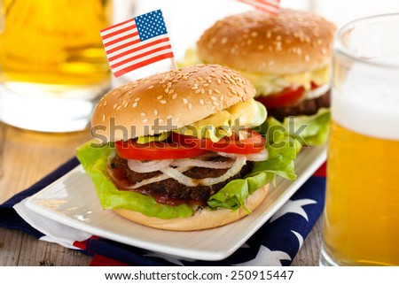 Beer and two tasty hamburgers with little American flags on top.  - stock photo