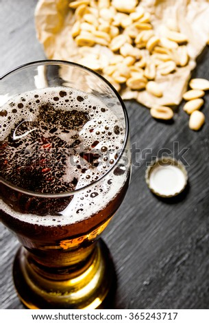Beer background. Beer with peanuts on the black wooden table. - stock photo