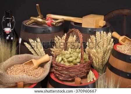 beer barrel, beer bottle, hammer and spigot with hops, wheat, grain, barley and malt - stock photo